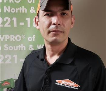 Nahum Rascon standing in front of a SERVPRO banner